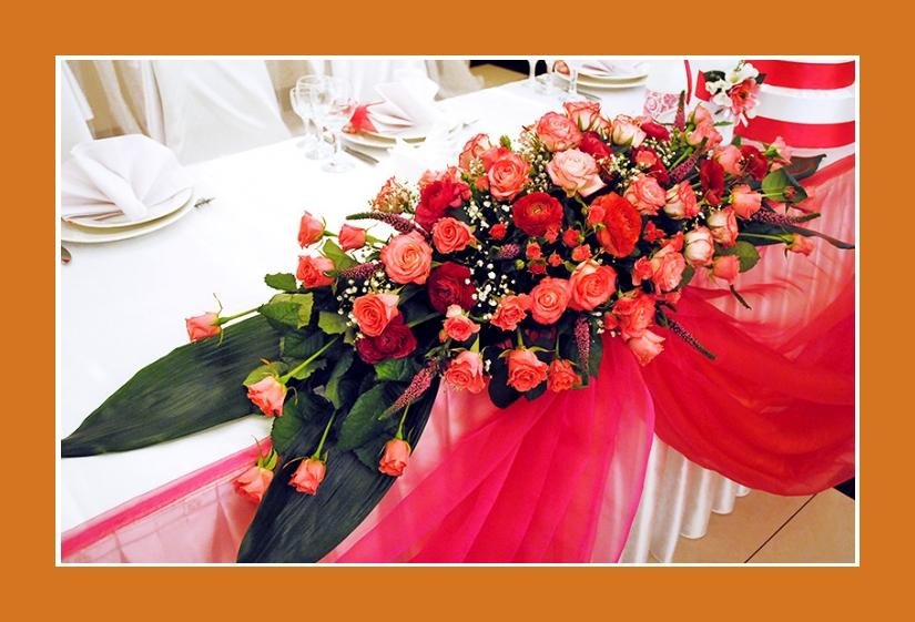 Blumenschmuck Hochzeitstafel mit lachspinken Rosen und himbeeroten Ranunkeln