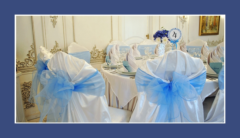 Stuhldeko mit Stuhlhussen und hellblauen luftigen Schleifen