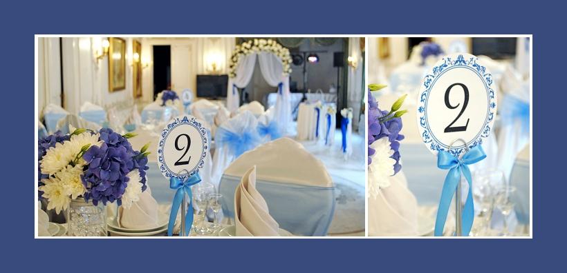 Tischnummern blau mit Schleifen neben Blumengestecken